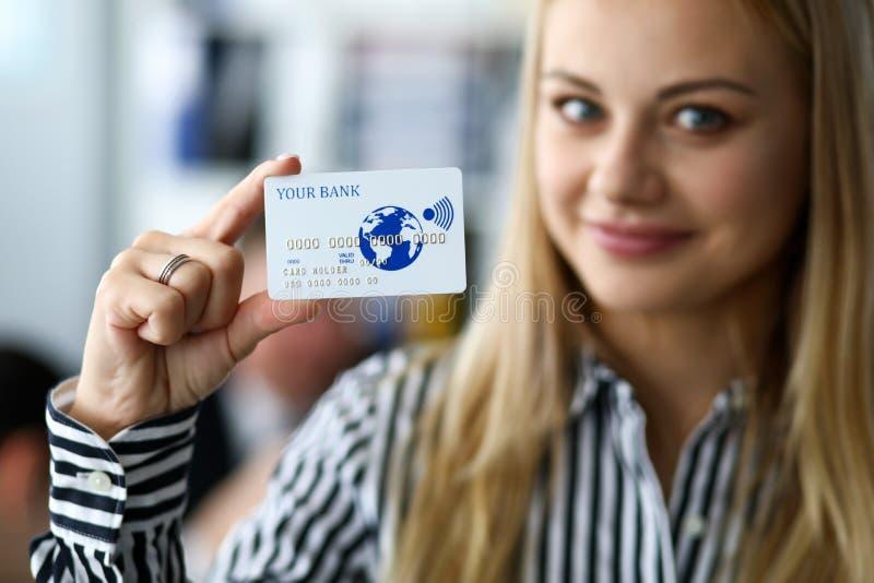 Η ευτυχής θηλυκή εκμετάλλευση αποτύπωσε υπό εξέταση την πλαστική κάρτα σε ανάγλυφο στοκ εικόνα