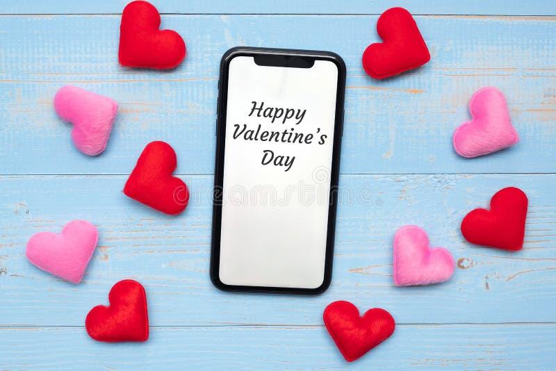 Η ευτυχής λέξη ημέρας Valentine's στην άσπρη επίδειξη οθονών επαφής του μαύρου έξυπνου τηλεφώνου με τις κόκκινες και ρόδινες κα στοκ εικόνες