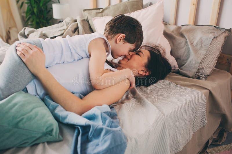 Η ευτυχής μητέρα αγκαλιάζει το γιο μικρών παιδιών της το πρωί, που κάθεται στο κρεβάτι στο σπίτι στοκ φωτογραφία