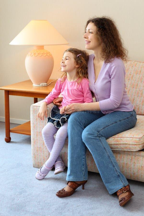 η ευτυχής μητέρα κορών καναπέδων κάθεται στοκ φωτογραφία με δικαίωμα ελεύθερης χρήσης