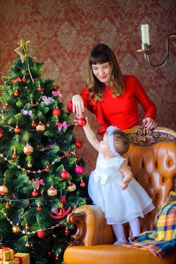Η ευτυχής μητέρα με μια μικρή κόρη διακοσμεί ένα εορταστικό χριστουγεννιάτικο δέντρο στοκ εικόνα με δικαίωμα ελεύθερης χρήσης