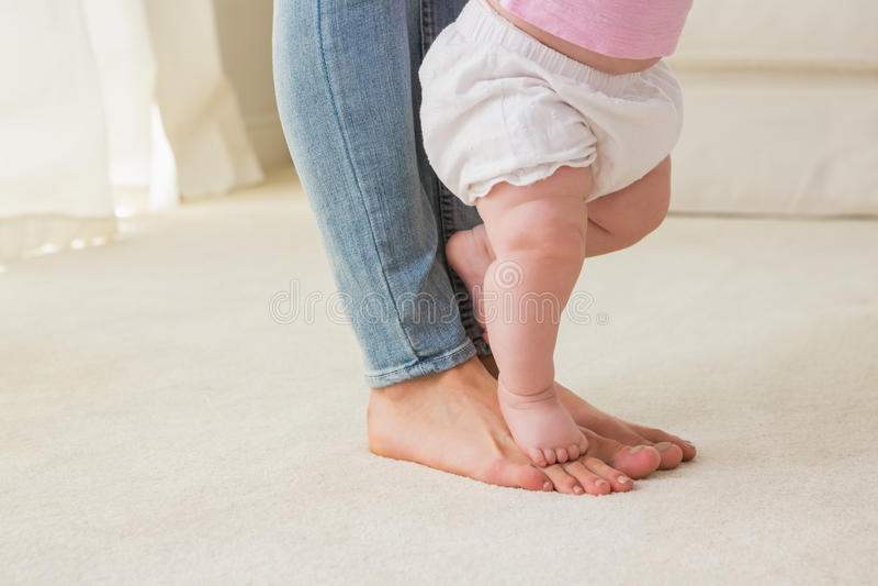 Η ευτυχής μητέρα με το κοριτσάκι της μαθαίνει να περπατά στοκ φωτογραφία