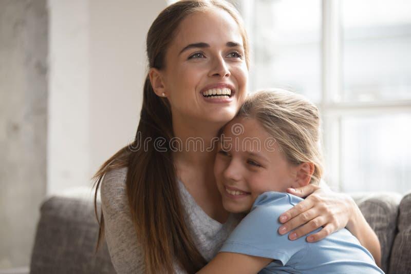 Η ευτυχής μητέρα που αγκαλιάζει λίγη οικογένεια κορών κάθεται στον καναπέ στοκ φωτογραφία με δικαίωμα ελεύθερης χρήσης