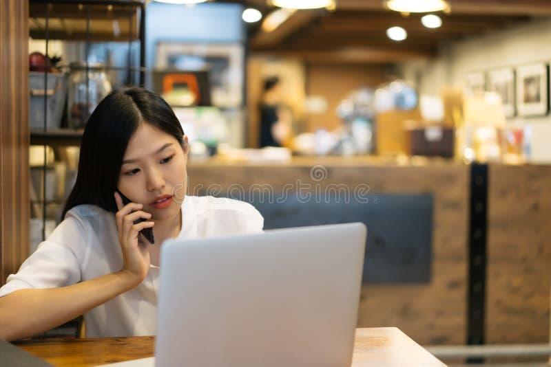 Η ευτυχής νέα ασιατική χρησιμοποίηση γυναικών τηλεφωνούν και η εργασία με ένα lap-top στο γραφείο καφέδων καφετεριών στοκ εικόνα με δικαίωμα ελεύθερης χρήσης