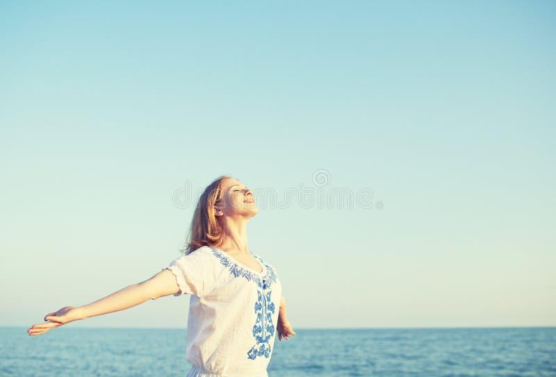Η ευτυχής νέα γυναίκα ανοίγει τις αγκάλες της στον ουρανό και τη θάλασσα στοκ φωτογραφία με δικαίωμα ελεύθερης χρήσης