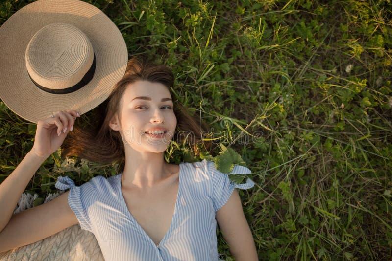 Η ευτυχής νέα γυναίκα βρίσκεται στο πάρκο στην πράσινη χλόη Άποψη πορτρέτου άνωθεν στοκ εικόνες