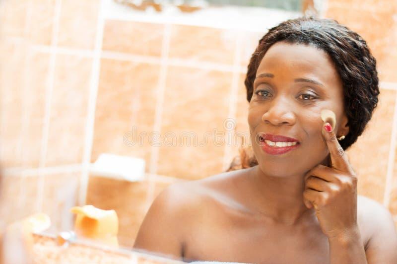Η ευτυχής νέα γυναίκα εφαρμόζει την κρέμα στο πρόσωπό της στοκ εικόνες