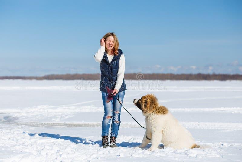 Η ευτυχής νέα γυναίκα και το καυκάσιο σκυλί ποιμένων της παίζουν στο χιόνι έξω στοκ εικόνες