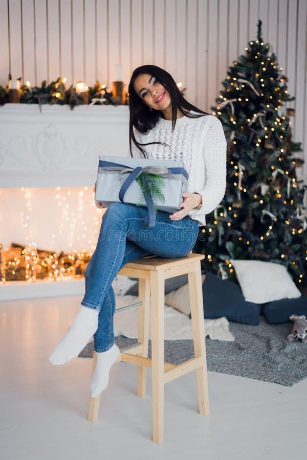 Η ευτυχής νέα γυναίκα με το δώρο Χριστουγέννων εξέπληξε και διέγειρε να καθίσει στο σπίτι ενάντια στις διακοσμήσεις Χριστουγέννων στοκ φωτογραφία με δικαίωμα ελεύθερης χρήσης
