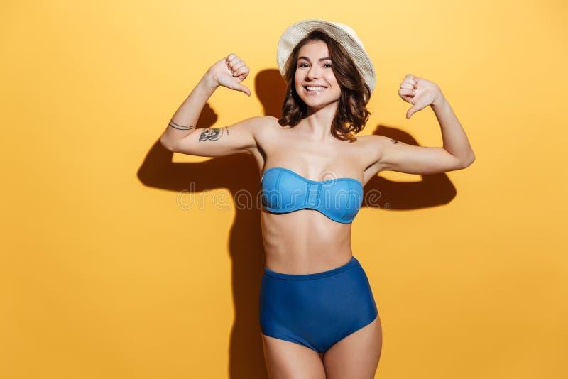 Η ευτυχής νέα γυναίκα στη swimwear παρουσίαση φυλλομετρεί κάτω στοκ εικόνες