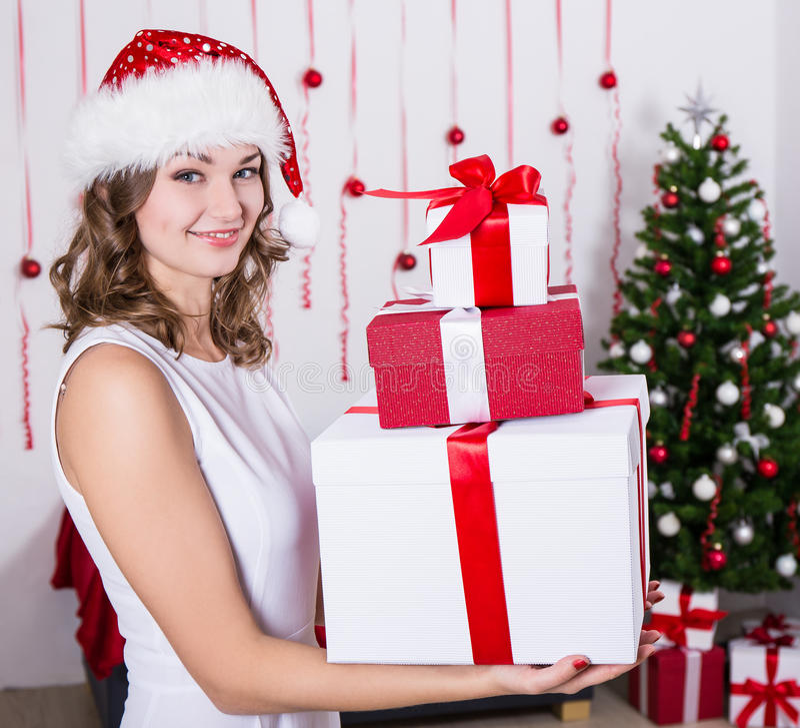 Download Η ευτυχής νέα γυναίκα στο καπέλο Santa με παρουσιάζει κοντά στο χριστουγεννιάτικο δέντρο Στοκ Εικόνα - εικόνα από χαρά, διακόσμηση: 62701723