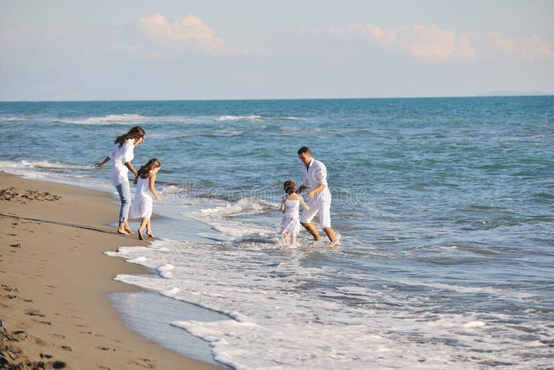 Η ευτυχής νέα οικογένεια έχει τη διασκέδαση στην παραλία στοκ εικόνα