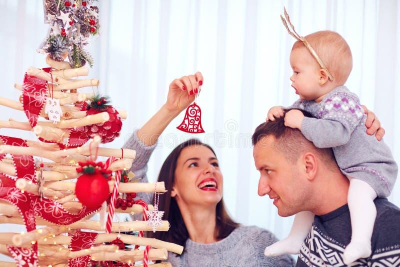 Η ευτυχής νέα οικογένεια διακοσμεί το χριστουγεννιάτικο δέντρο eco στο σπίτι στοκ εικόνες με δικαίωμα ελεύθερης χρήσης