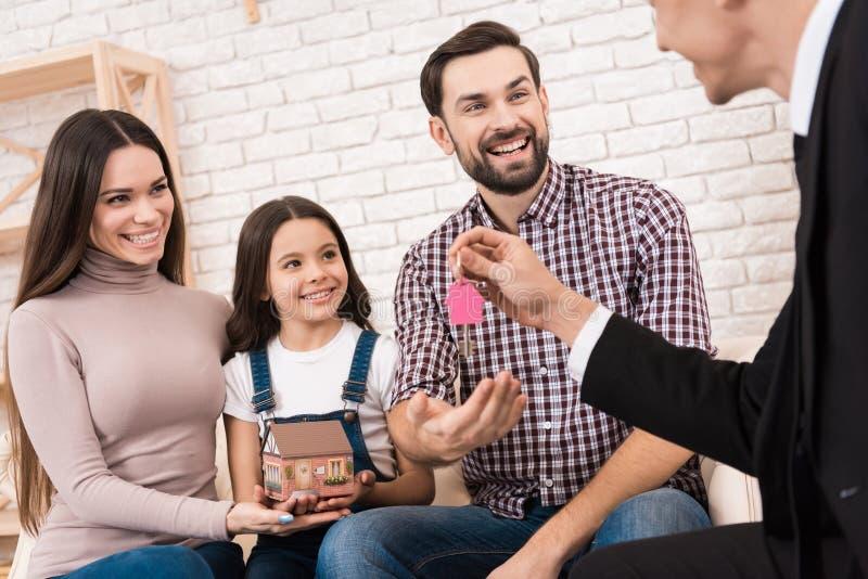 Η ευτυχής νέα οικογένεια φτάνει τα κλειδιά στο καινούργιο σπίτι, το οποίο το realtor βοήθησε να επιλέξει αγοράζει το οικογενε&iot στοκ εικόνα