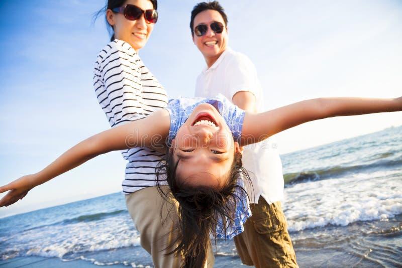 Η ευτυχής οικογένεια απολαμβάνει τις θερινές διακοπές στην παραλία στοκ εικόνα