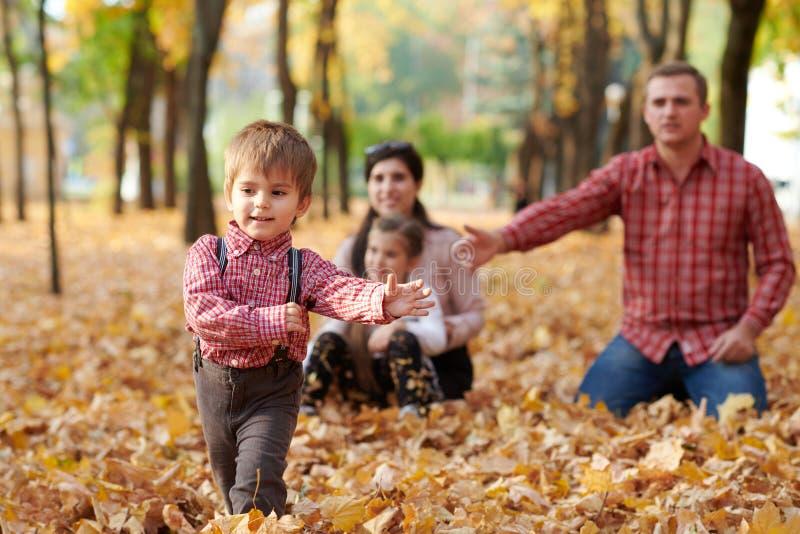 Η ευτυχής οικογένεια είναι στο πάρκο πόλεων φθινοπώρου Παιδιά και πρόγονοι Αυτοί που θέτουν, που χαμογελούν, που παίζουν και που  στοκ εικόνα με δικαίωμα ελεύθερης χρήσης