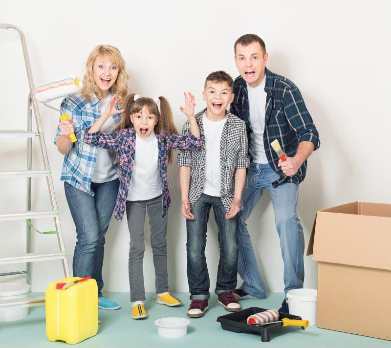 Η ευτυχής οικογένεια κάνει τις επισκευές στο σπίτι στοκ εικόνες