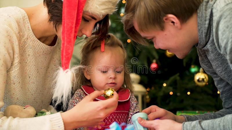 Η ευτυχής οικογένεια με ένα παιδί περνά τα Χριστούγεννα από κοινού Παιχνίδι γονέων και κορών στο σπίτι κοντά στο χριστουγεννιάτικ στοκ φωτογραφία με δικαίωμα ελεύθερης χρήσης