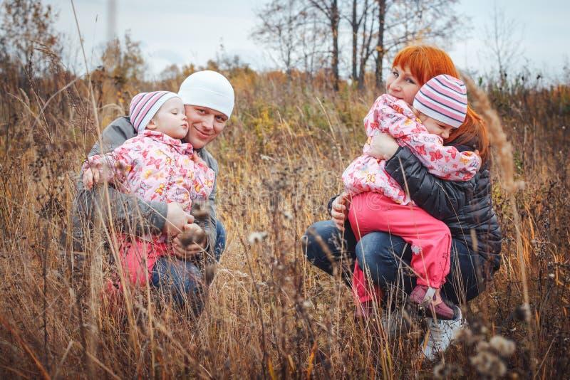Η ευτυχής οικογένεια με δύο 1χρονα κορίτσια έχει το υπόλοιπο σε έναν κίτρινο τομέα στοκ φωτογραφία