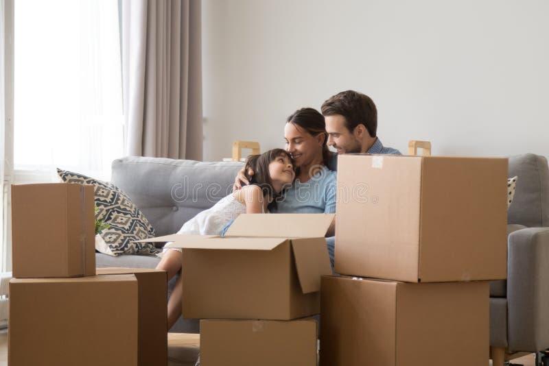 Η ευτυχής οικογένεια με την κόρη χαλαρώνει στον καναπέ στην κίνηση της ημέρας στοκ φωτογραφία