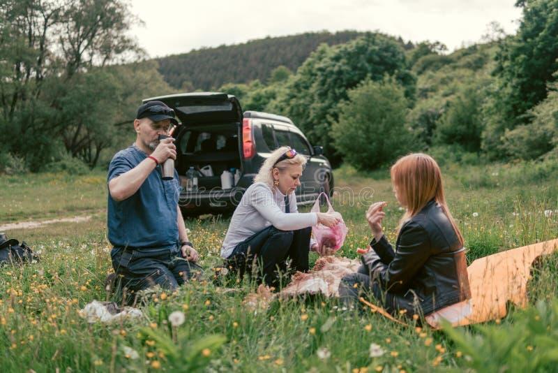 Η ευτυχής οικογένεια που έχει το μεσημεριανό γεύμα και πίνει το τσάι στρατοπέδευση, Σαββατοκύριακο, πικ-νίκ άνδρας, γυναίκα, κορί στοκ φωτογραφία