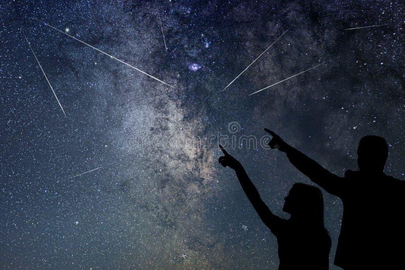 Η ευτυχής οικογένεια προσέχει το ντους μετεωριτών Κοντά ουρανός στοκ εικόνες