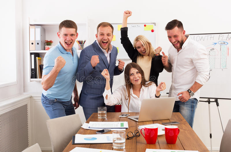 Η ευτυχής ομάδα επιχειρηματιών γιορτάζει την επιτυχία στο γραφείο στοκ εικόνα