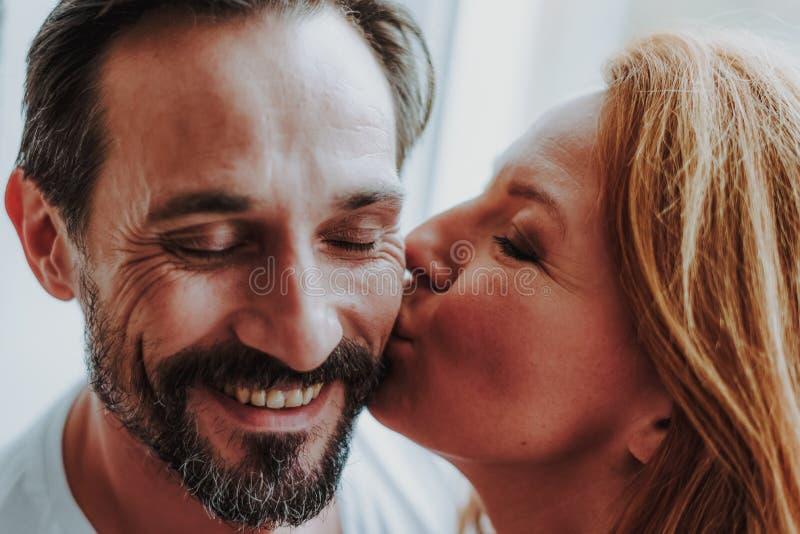 Η ευτυχής ρομαντική γυναίκα tenderly φιλά τον άνδρα στοκ εικόνα
