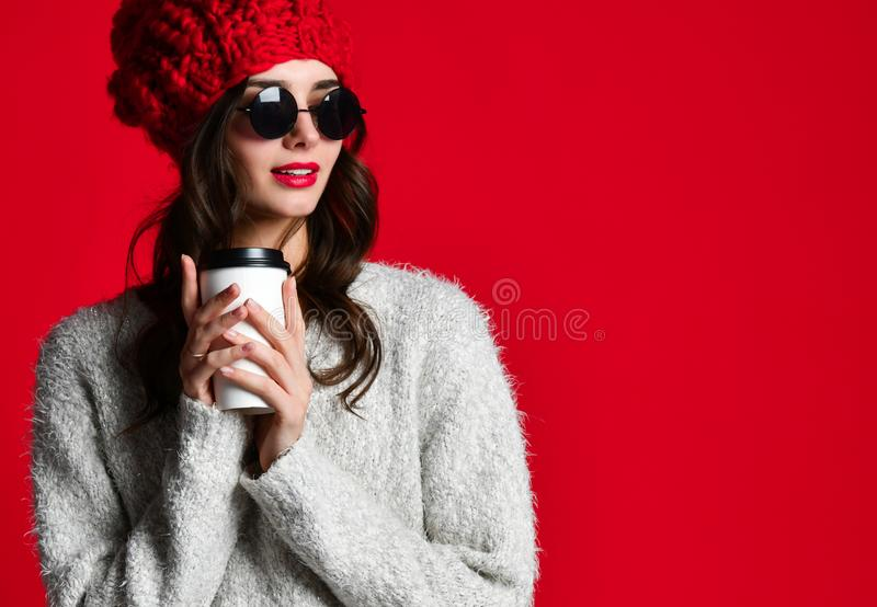 Η ευτυχής χαμογελώντας γυναίκα μόδας κρατά το φλυτζάνι καφέ στο κόκκινο υπόβαθρο τοίχων στοκ εικόνες με δικαίωμα ελεύθερης χρήσης