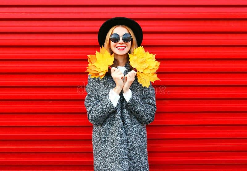 Η ευτυχής χαμογελώντας γυναίκα φθινοπώρου μόδας κρατά τα κίτρινα φύλλα σφενδάμου στοκ εικόνα