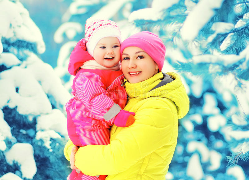 Η ευτυχής χαμογελώντας μητέρα χειμερινού πορτρέτου κρατά ότι το μωρό παραδίδει επάνω το χιονώδες χριστουγεννιάτικο δέντρο στοκ φωτογραφία