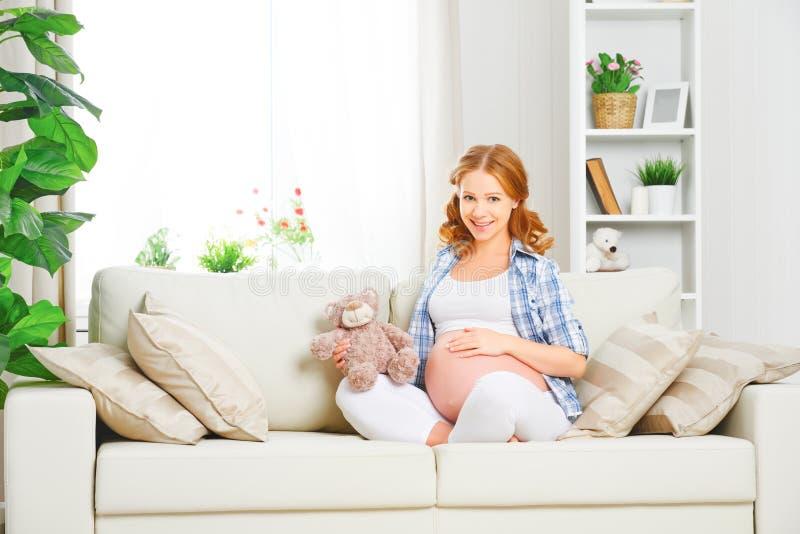 Η ευτυχής χαλάρωση εγκύων γυναικών στο σπίτι με το παιχνίδι teddy αντέχει στοκ φωτογραφία με δικαίωμα ελεύθερης χρήσης