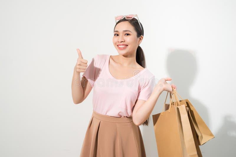 Η ευτυχής ψωνίζοντας νέα γυναίκα παρουσιάζει αντίχειρα με τις τσάντες - που απομονώνονται στο άσπρο υπόβαθρο, ασιατικό πρότυπο στοκ εικόνες