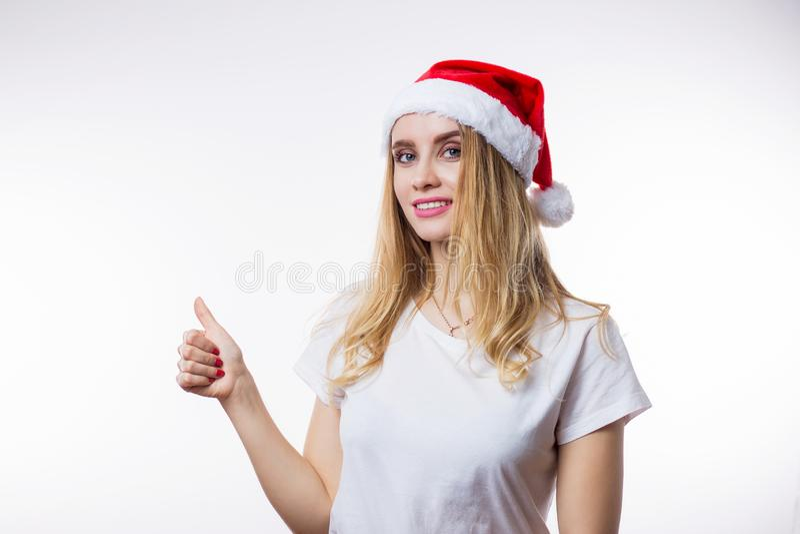 Η ευτυχής όμορφη γυναίκα στο κόκκινο καπέλο Santa παρουσιάζει αντίχειρα σημαδιών στο άσπρο υπόβαθρο με το διάστημα αντιγράφων στοκ φωτογραφία με δικαίωμα ελεύθερης χρήσης