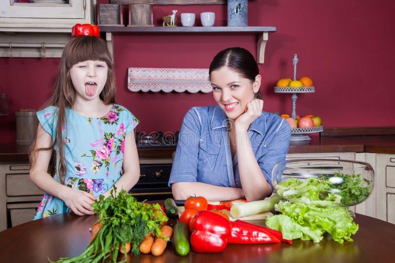 Η ευτυχείς μητέρα και η κόρη απολαμβάνουν και το υγιές γεύμα μαζί στην κουζίνα τους στοκ εικόνα