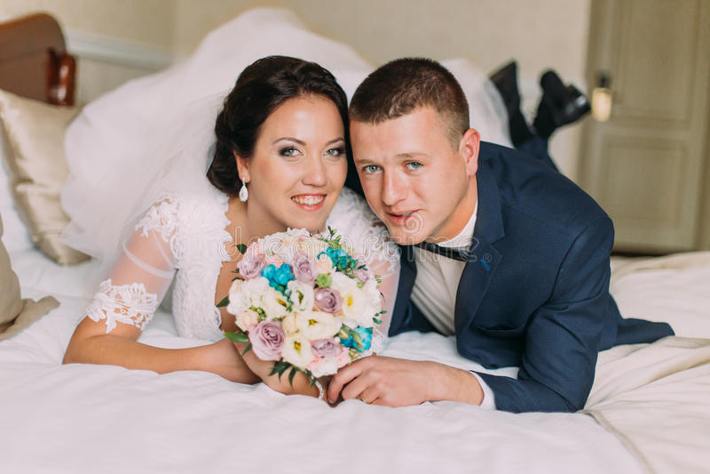 Η ευτυχείς νύφη και ο νεόνυμφος βάζουν στο κρεβάτι στο δωμάτιο ξενοδοχείου μετά από το γαμήλιο εορτασμό Newlyweds στο μήνα του μέ στοκ φωτογραφία με δικαίωμα ελεύθερης χρήσης