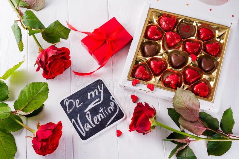 Η ευχετήρια κάρτα ημέρας βαλεντίνων με τα κόκκινα τριαντάφυλλα και η καρδιά διαμόρφωσαν τη σοκολάτα στο ξύλινο υπόβαθρο Τοπ όψη στοκ εικόνα με δικαίωμα ελεύθερης χρήσης