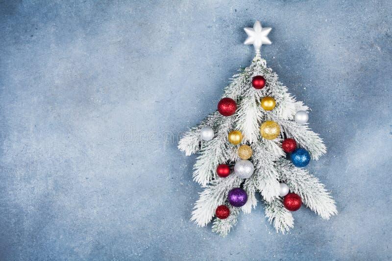 Η ευχετήρια κάρτα με το δημιουργικό δέντρο έλατου Χριστουγέννων διακόσμησε το αστέρι και τις ζωηρόχρωμες σφαίρες στην μπλε τοπ άπ στοκ φωτογραφία με δικαίωμα ελεύθερης χρήσης