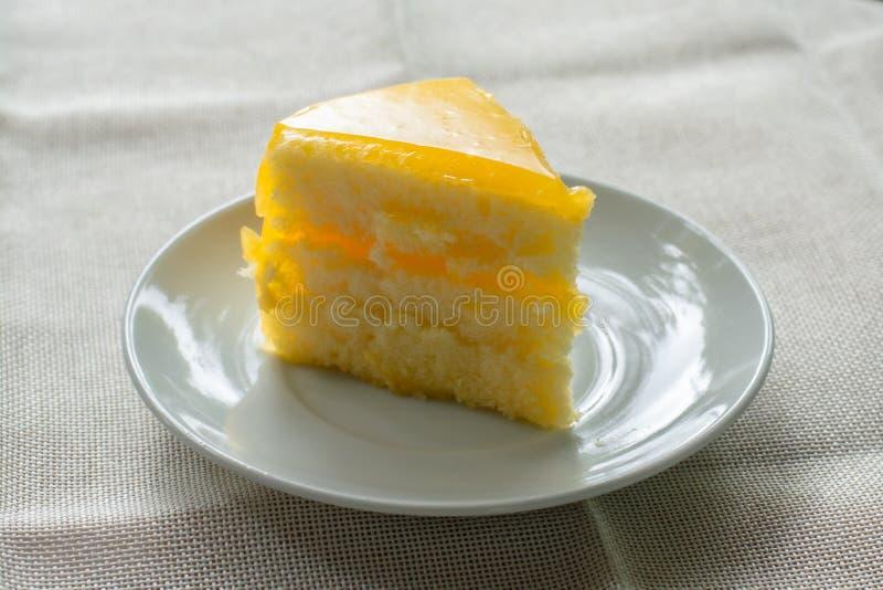 Η εύγευστη φέτα του πορτοκαλιού κέικ εξυπηρέτησε στο άσπρο πιάτο στους χρόνους καφέ στο τραπεζομάντιλο στοκ εικόνα με δικαίωμα ελεύθερης χρήσης