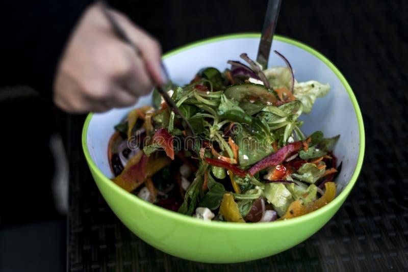 Η εύγευστη φρέσκια υγιής σαλάτα σε ένα πράσινο κύπελλο που αναμιγνύεται από μια γυναίκα δίνει με τα τρόφιμα κουταλιών σαλάτας στοκ εικόνα με δικαίωμα ελεύθερης χρήσης