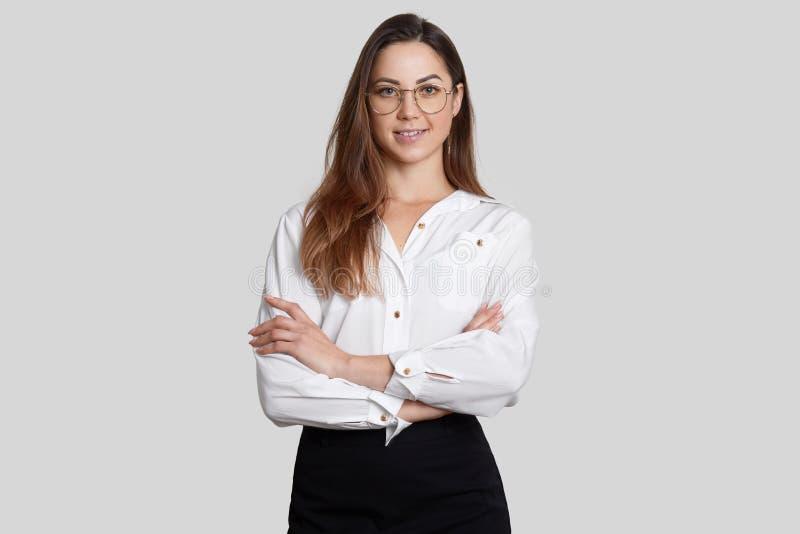 Η εύθυμη γεμάτη αυτοπεποίθηση επιχειρηματίας φορά την άσπρη μπλούζα και η μαύρη φούστα, κρατά τα όπλα διπλωμένα, φορά γύρω από τα στοκ φωτογραφία με δικαίωμα ελεύθερης χρήσης