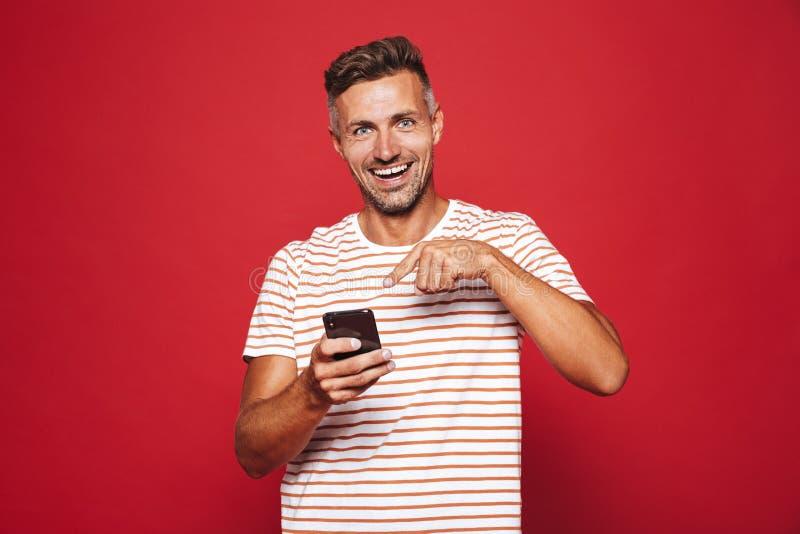 Η εύθυμη δεκαετία του '30 ατόμων στη ριγωτή μπλούζα που χαμογελά και που κρατά το κινητό π στοκ φωτογραφίες με δικαίωμα ελεύθερης χρήσης
