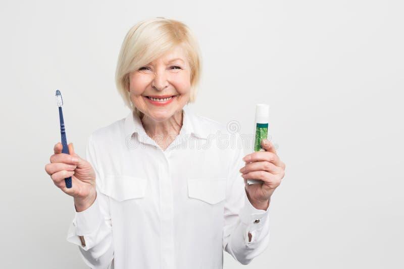 Η εύθυμη και ευτυχής γυναίκα κρατά μια οδοντόπαστα και μια οδοντόβουρτσα Παρουσιάζει χαμόγελο beautifyl της Στο λευκό στοκ φωτογραφία