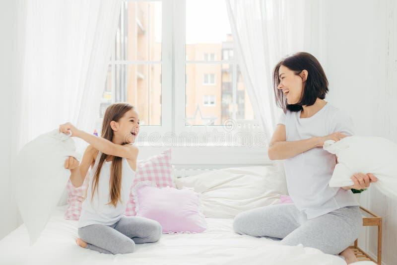 Η εύθυμη μητέρα και daugher έχει τη διασκέδαση μαζί, έχει την πάλη μαξιλαριών στοκ φωτογραφία με δικαίωμα ελεύθερης χρήσης