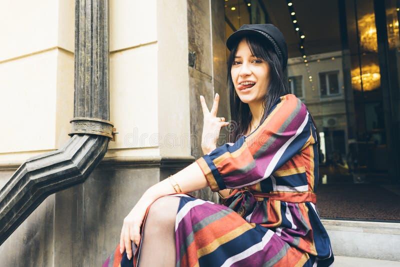 Η εύθυμη νέα γυναίκα κάθεται στα βήματα μιας μπουτίκ που παρουσιάζει γλώσσα στοκ φωτογραφία με δικαίωμα ελεύθερης χρήσης
