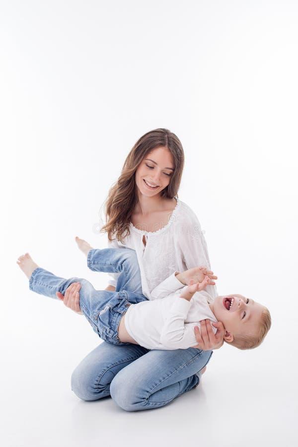 Η εύθυμη νέα γυναίκα παίζει με το παιδί της στοκ φωτογραφίες με δικαίωμα ελεύθερης χρήσης