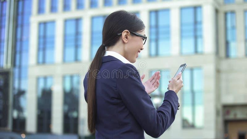 Η εύθυμη νέα γυναίκα που διαβάζει τις καλές ειδήσεις τηλεφωνά, επιτυχής επιχειρησιακή κυρία, σταδιοδρομία στοκ εικόνες