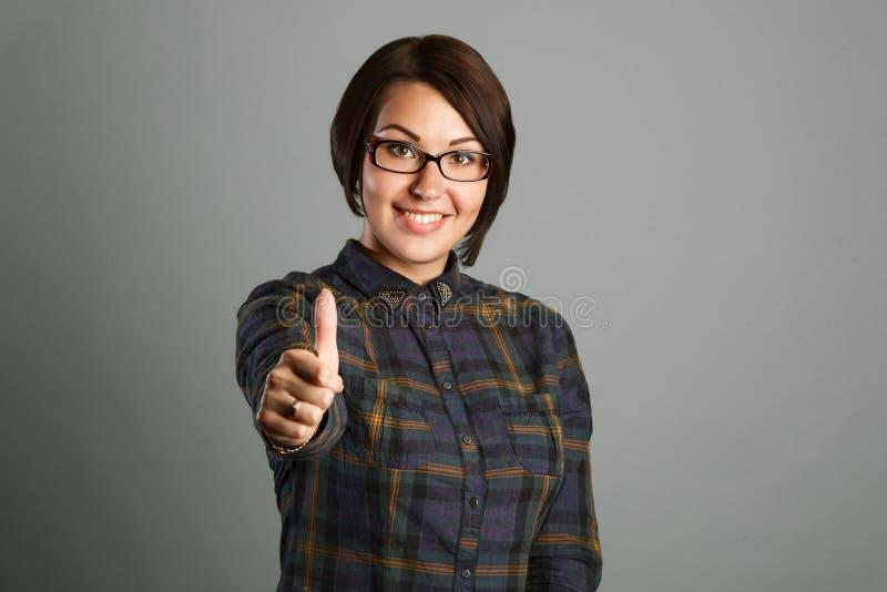 Η εύθυμη νέα γυναίκα που παρουσιάζει αντίχειρα υπογράφει επάνω στο γκρίζο υπόβαθρο στοκ εικόνες
