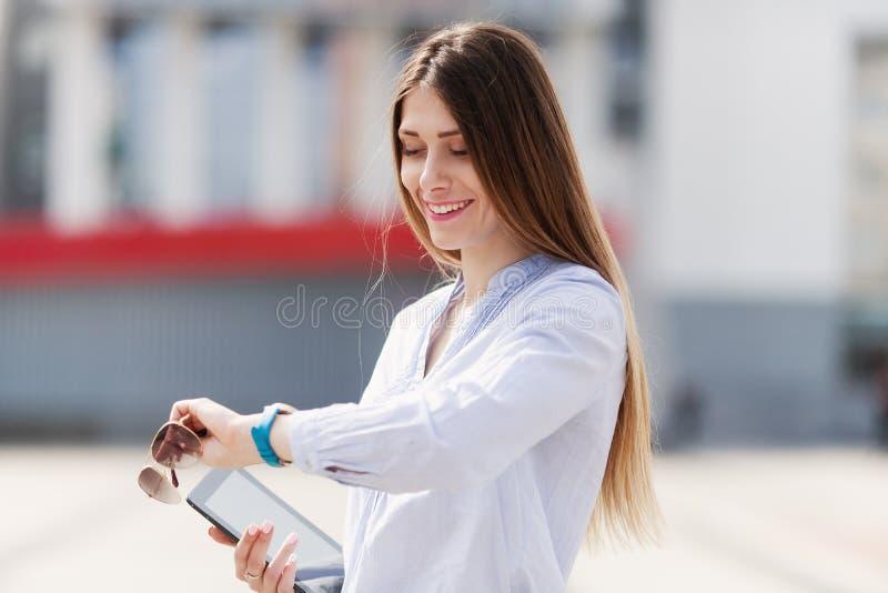 Η εύθυμη νέα όμορφη γυναίκα μέσα στο μπλε πουκάμισο κρατά το touchpad της με το χαμόγελο και εξετάζει το ρολόι του στοκ εικόνες