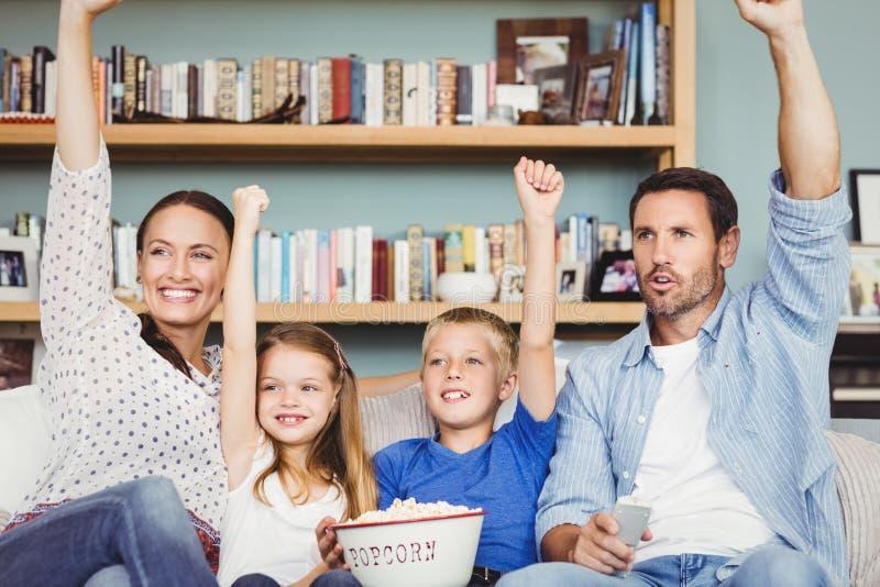 Η εύθυμη οικογένεια με τα όπλα αύξησε καθμένος στον καναπέ στοκ εικόνες με δικαίωμα ελεύθερης χρήσης